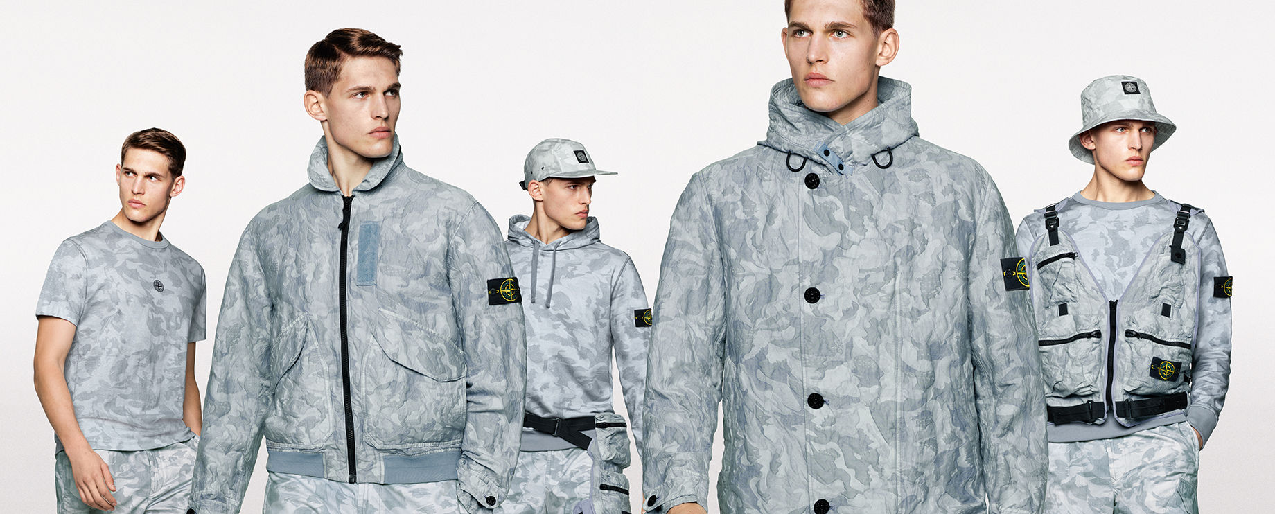 Five shots of the same model, showing the front and side view of him wearing different styles of sweatshirts, pants, jackets, hats, t shirt and vest, all in the same gray camouflage print.