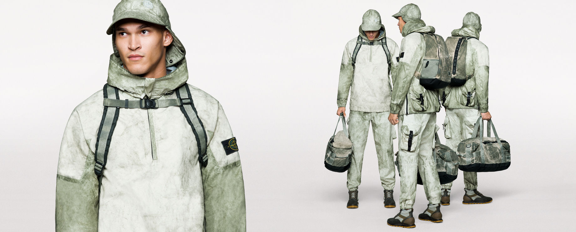 Four images of the same model, showing the close up, front, side and back view of him wearing pants, a parka with high collar, a cap with neck flap, a backpack with sternum strap and carrying a duffle bag, all in a matching khaki and green pattern.