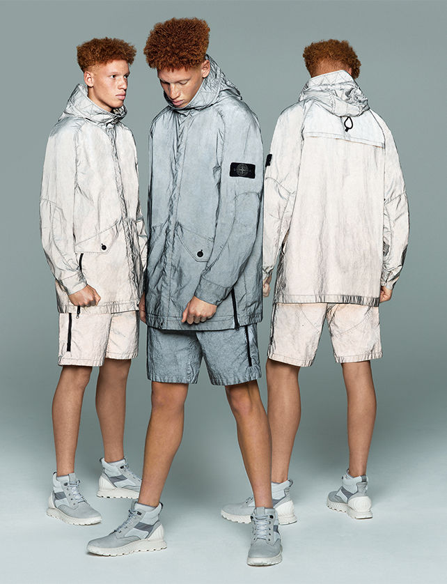 Three models, two showing front and back of the same reflective white shorts and matching hooded jacket, the third one, showing the front of gray reflective shorts and hooded jacket.