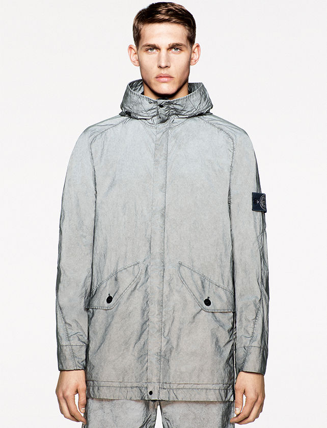 Model wearing a light gray reflective jacket with hood and two flap pockets with button closure.