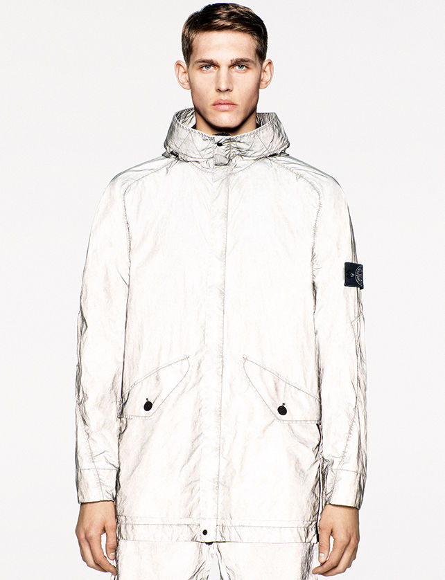Model wearing a white reflective jacket with hood and two flap pockets with button closure.