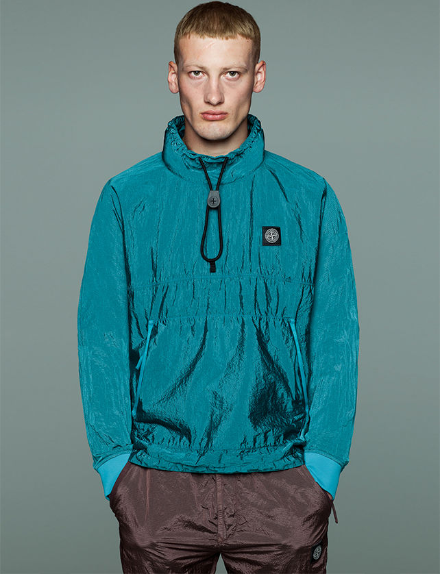 Model wearing brown pants and a high collar blue jacket with neck drawstring, zippered side pockets and Stone Island patch at left chest.