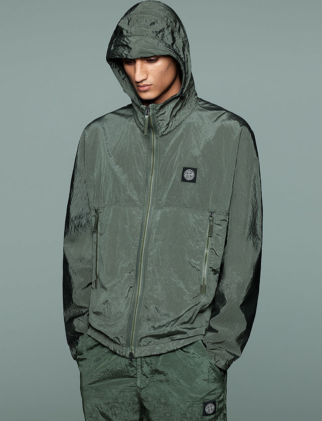 Model wearing matching green pants and hooded jacket with zipper closure, zippered side pockets and Stone Island patch at left chest.