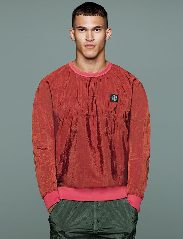Model wearing a red crewneck sweatshirt with ribbed neck, cuffs and hem and Stone Island patch at left chest.