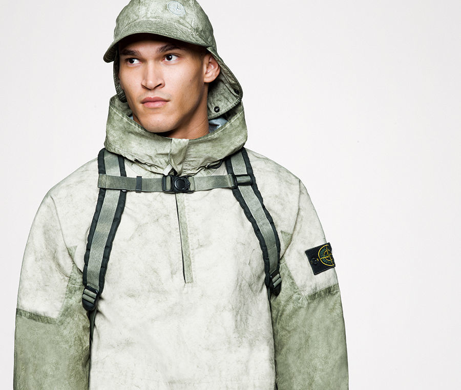 Model wearing a parka with high collar, a cap with neck flap and a backpack with sternum strap, all in a matching khaki and green pattern.