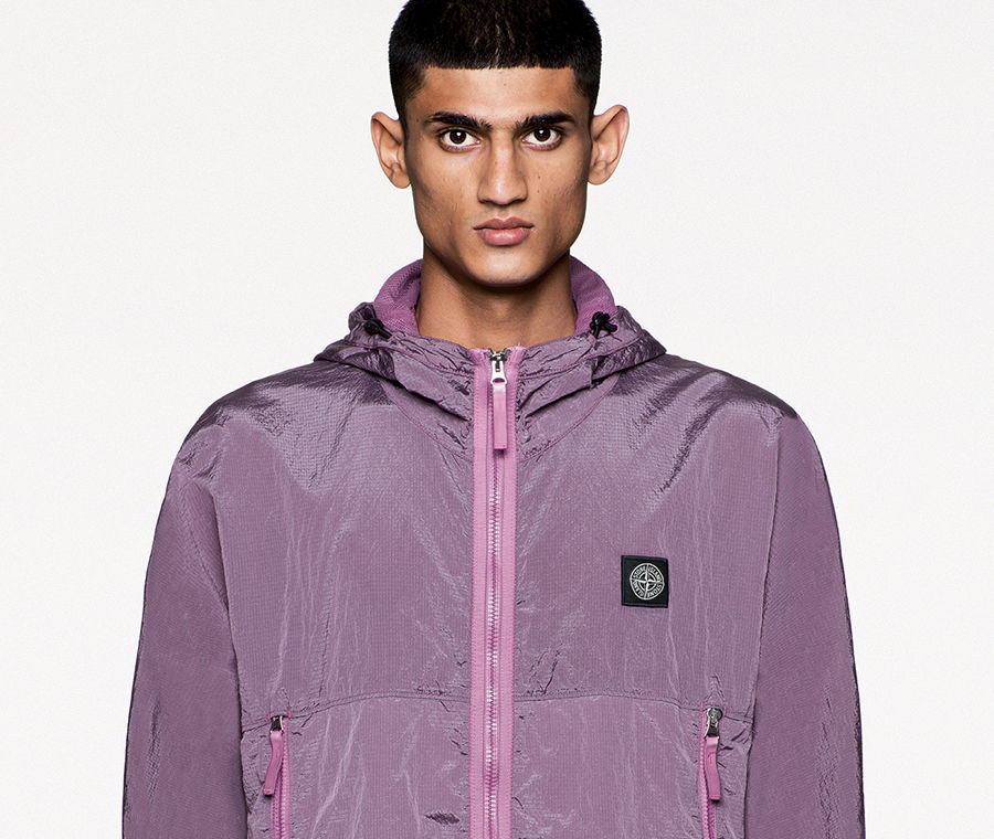 Model wearing a hooded purple jacket with zipper closure, zippered side pockets and Stone Island patch at left chest.