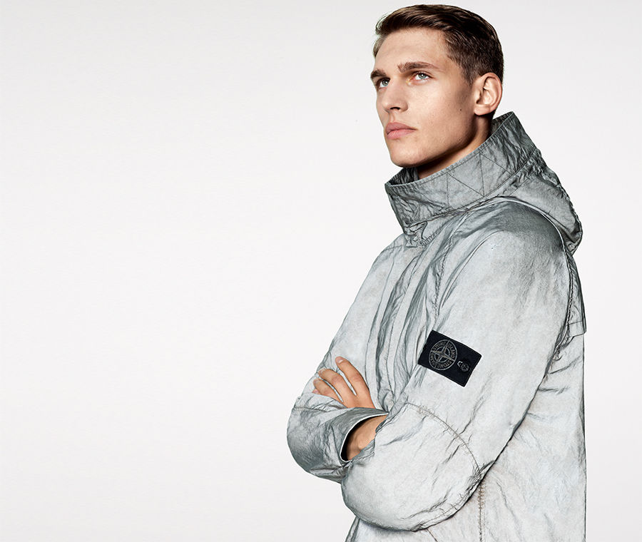 Model wearing a light gray reflective jacket with hood and Stone Island badge on upper left arm.
