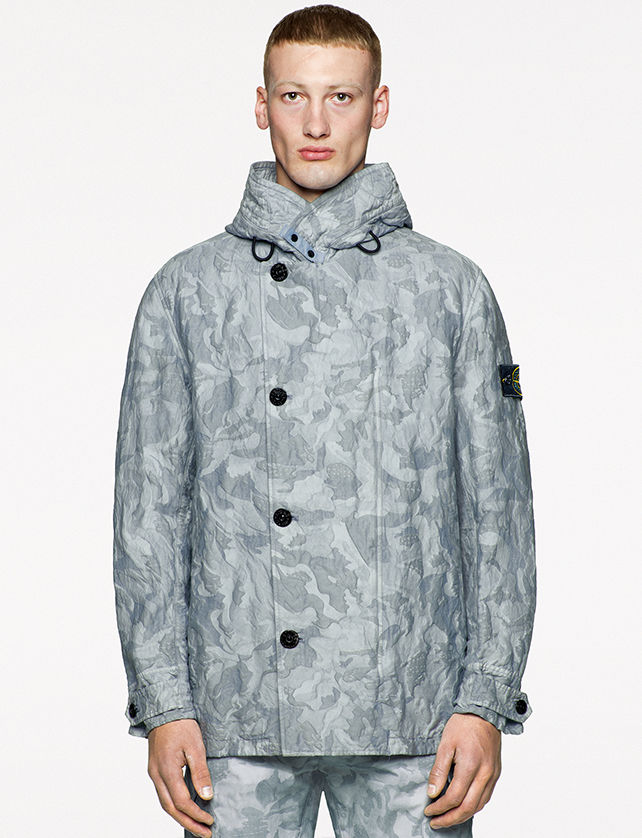 Model wearing pants and a high collar jacket with asymmetrical button closure, both in the same gray camouflage print.