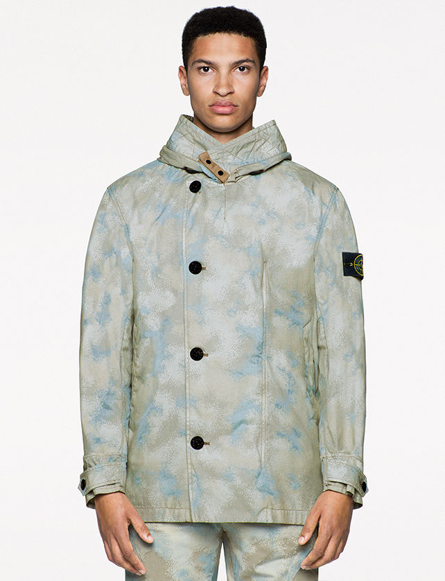 Model wearing pants and a high collar jacket with asimmetrical button closure, both in the same khaki and light blue camouflage print.