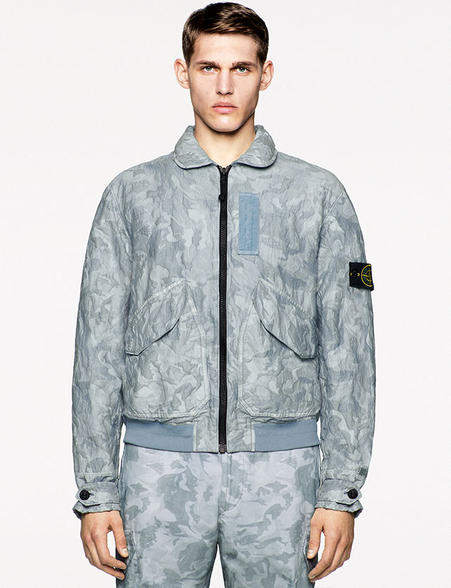 Model wearing pants and a bomber jacket with round collar, zipper closure and flap pockets, both in the same gray camouflage print.