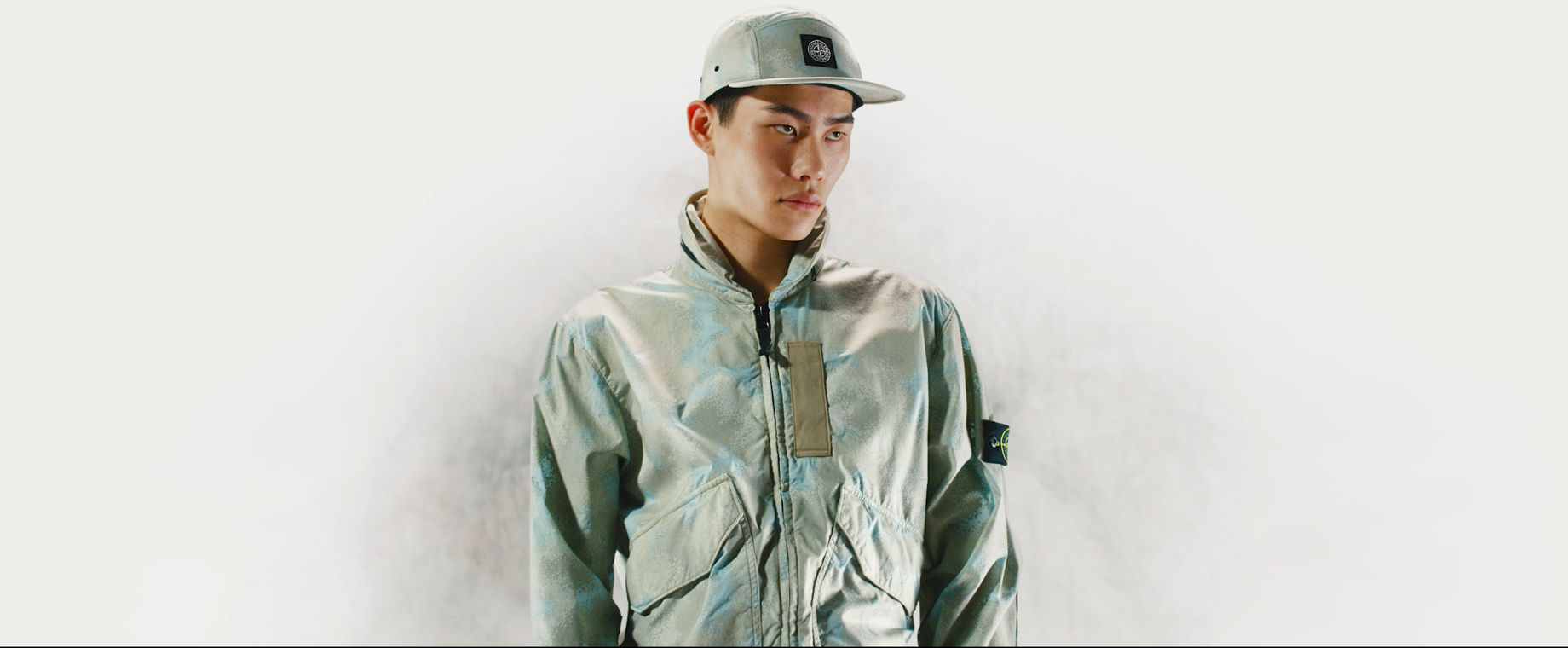 Model wearing a cap and a jacket with high collar, zipper closure and patch pockets, both in the same khaki and light blue camouflage print.