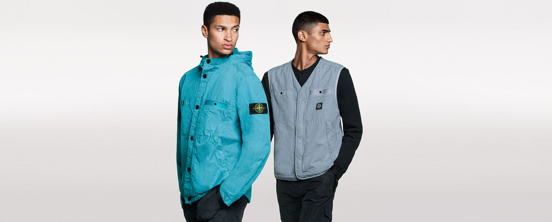 Two models, one wearing black pants and a bright blue hooded jacket with button closure, two patch pockets and two side pockets, the other one wearing black pants, a black shirt and a gray V neck vest with two patch pockets and two side pockets.
