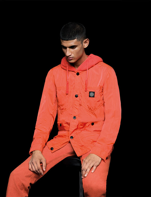 Model wearing bright orange pants and a matching hooded jacket with button closure, patch pockets and Stone Island patch on left chest.