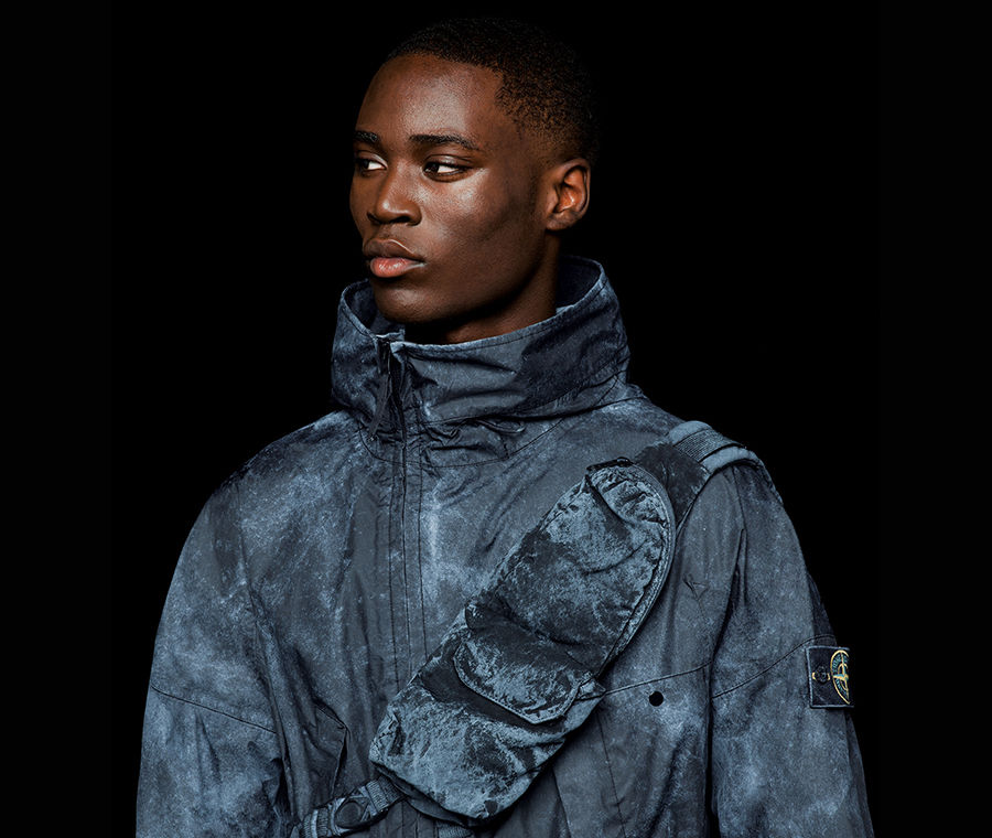 Model wearing a bright blue jacket with stand collar, four flap pockets on the front with black buttons, Stone Island patch in the center of the chest
