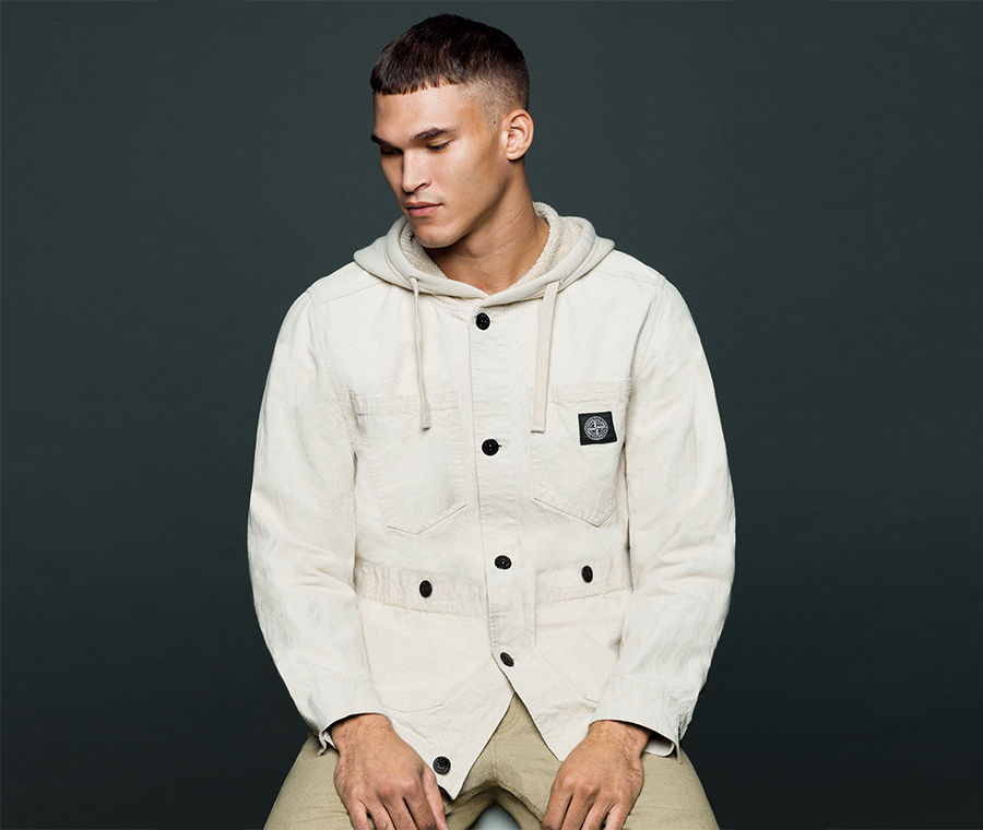 Model wearing beige pants and an off white hooded jacket with button closure and Stone Island patch on left chest.