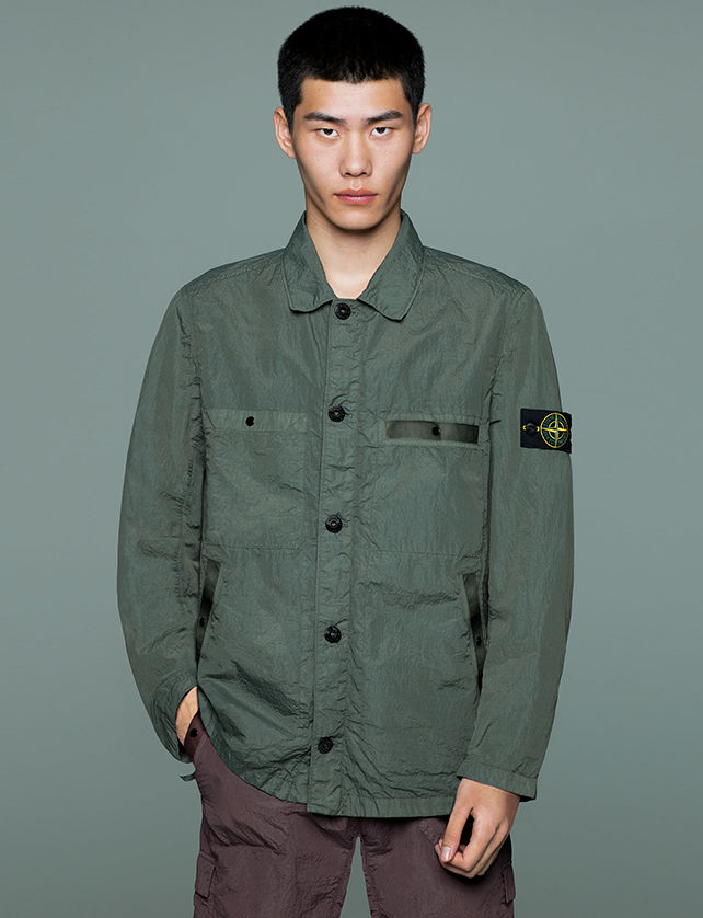 Model wearing dark brown pants and a military green jacket with collar, button closure, two patch pockets and two side pockets.