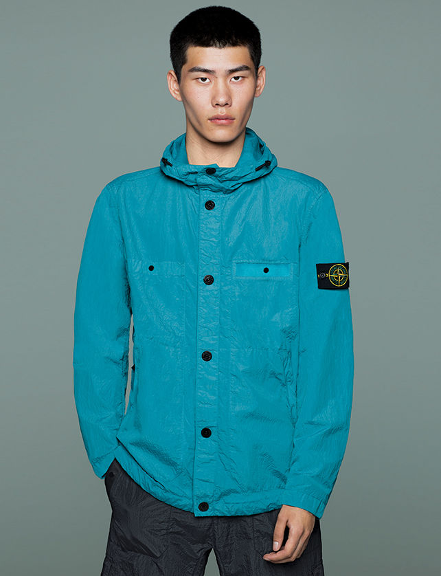 Model wearing black pants and a bright blue hooded jacket with button closure, two patch pockets, two side pockets and Stone Island badge on upper left arm.