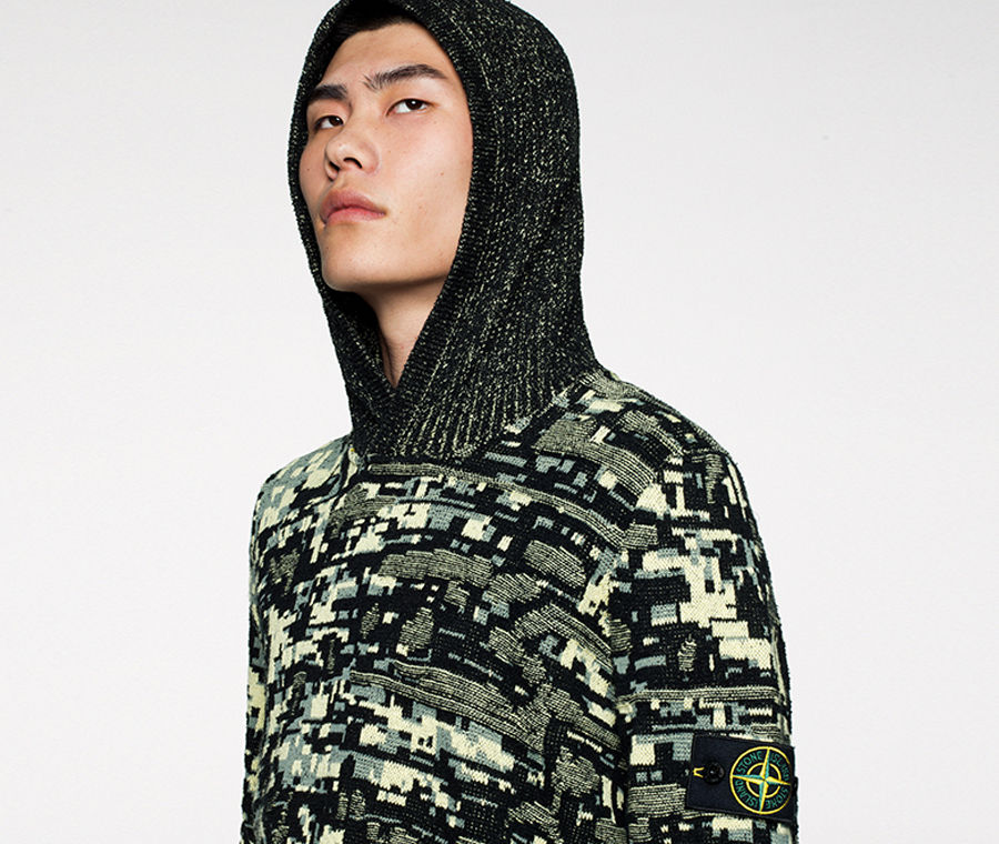 Model wearing a green and black hooded sweater woven to resemble a pixelated camouflage.