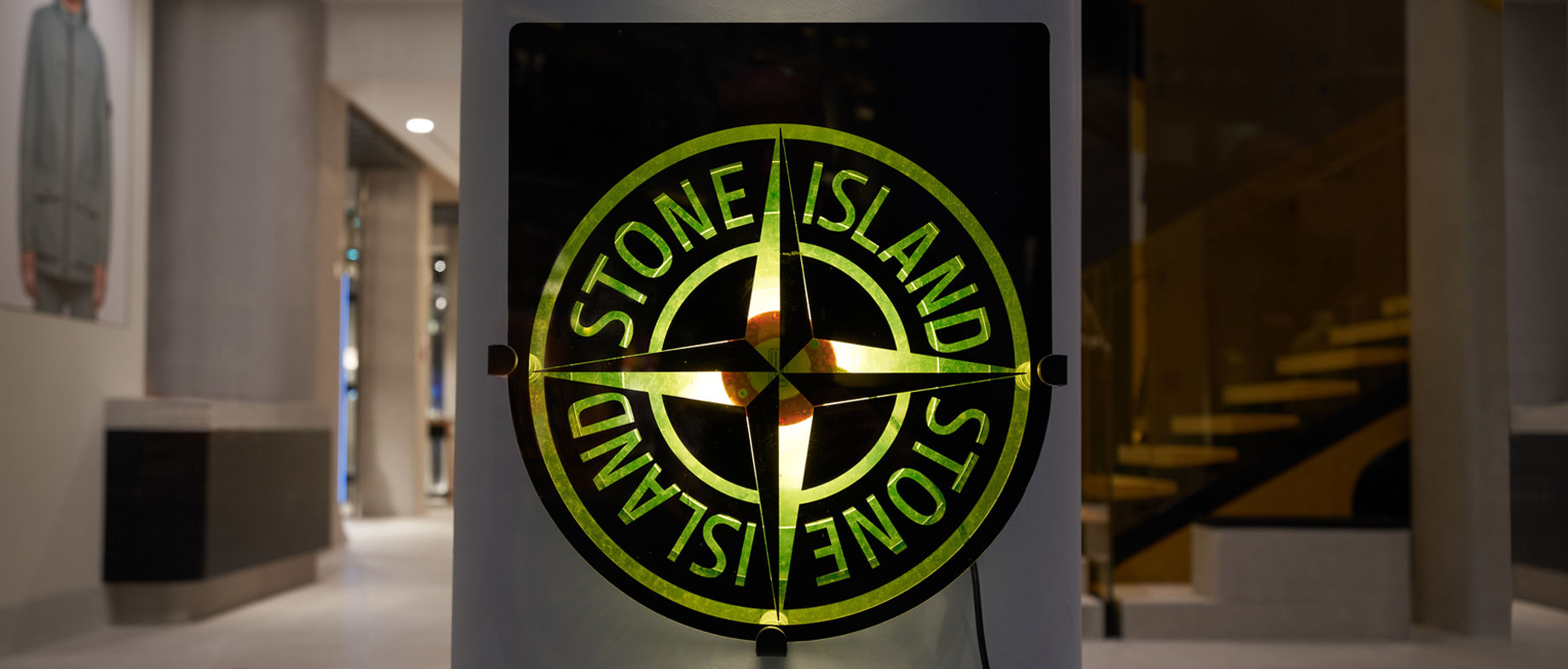 Back lit Stone Island compass rose logo with interior of a modern store as a background.