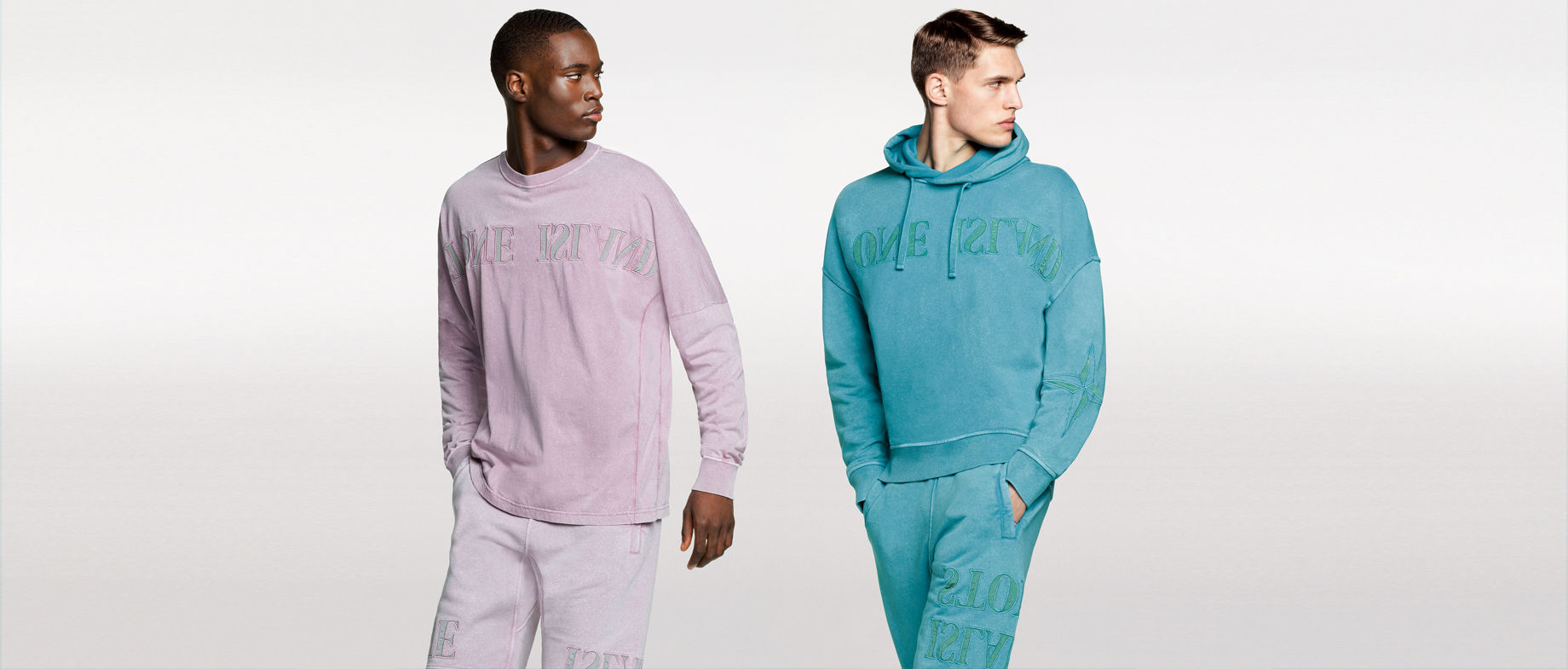 Two models, one wearing a pink crewneck sweatshirt and matching sweatpants, the other one wearing a light blue hooded sweatshirt with matching sweatpants, both with mirrored Stone Island embroidery across the chest and on the thighs.