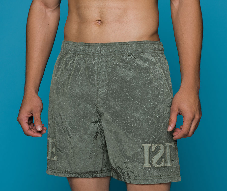 Lower body shot of model wearing olive green flecked swim trunks with elasticated waistband, slanting hand pockets and lettering embroidery on the legs.