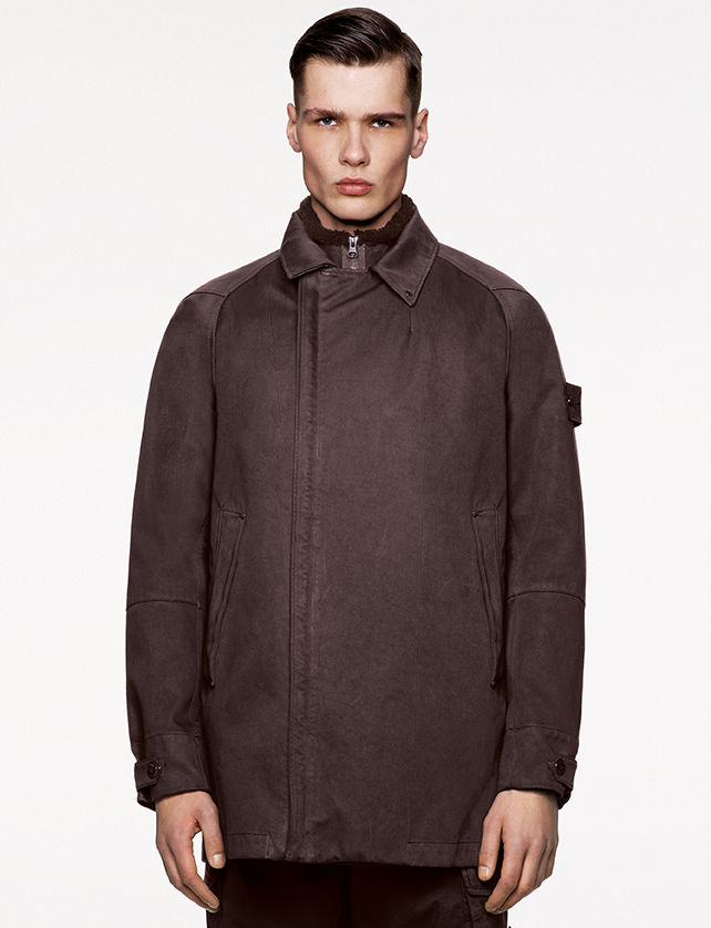 Model wearing a dark brown mid length coat with shirt collar, concealed zipper closure and two slanting hand pockets.