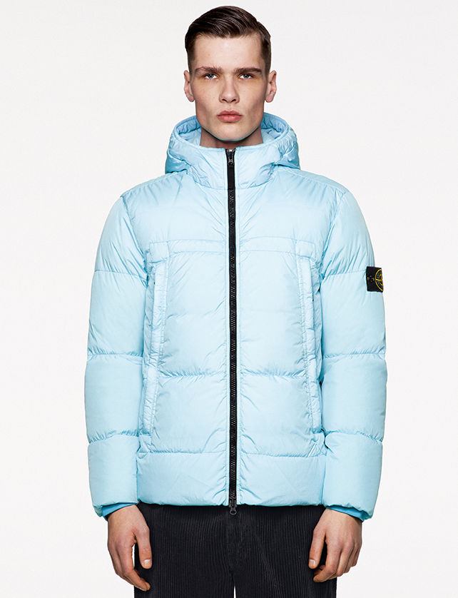 Model wearing black ribbed pants and a light blue down jacket with hood, black zipper fastening and the Stone Island badge on upper left arm.