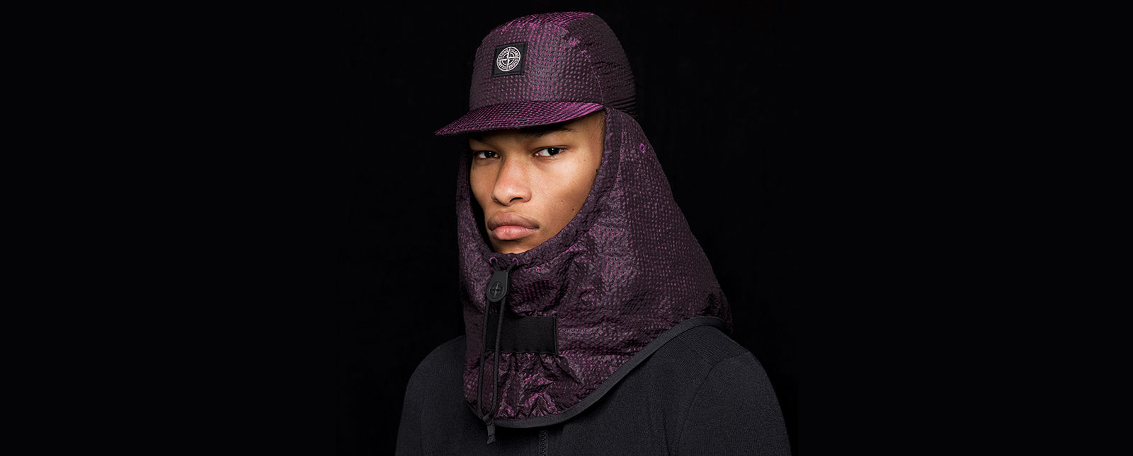 Model wearing a purple cap with neck and back flap with drawstring and the Stone Island patch on the forehead.