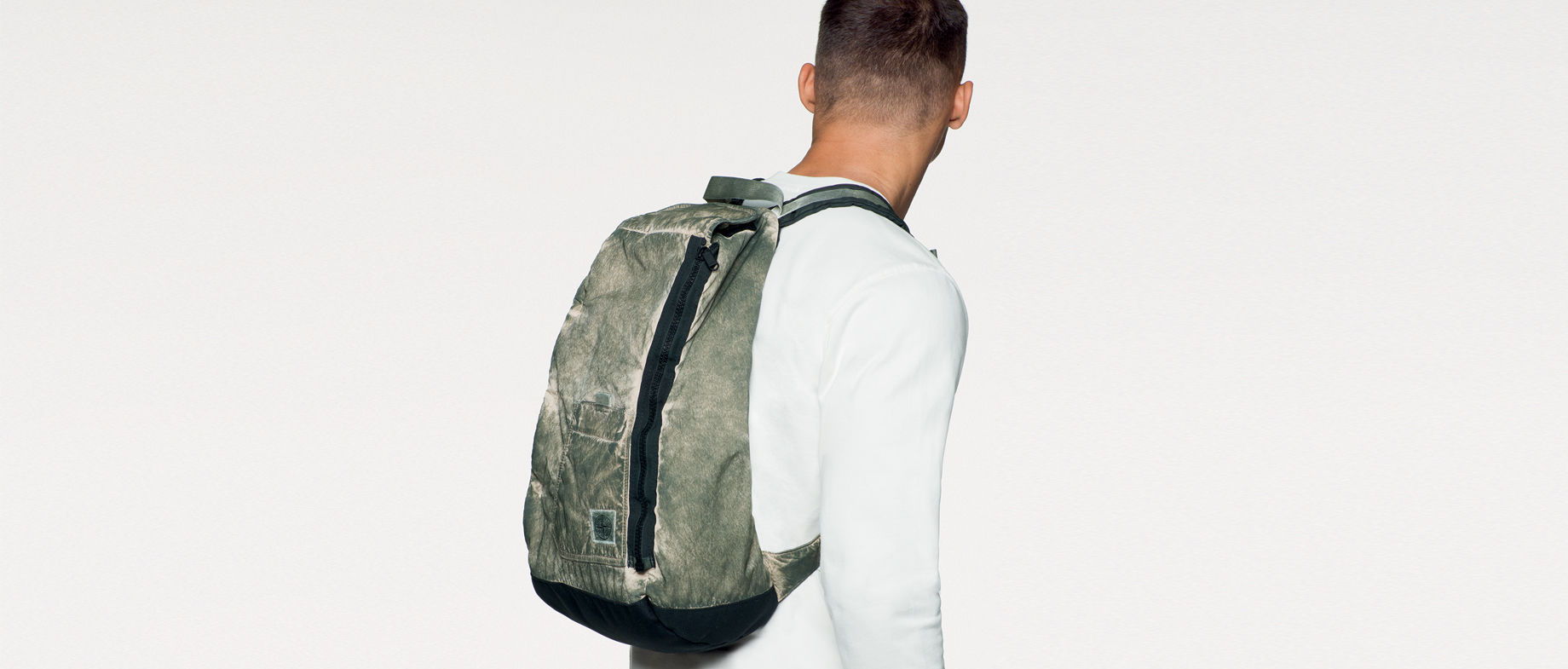 Back view of model wearing a white sweatshirt and a dark green, dust color effect backpack with top handle, shoulder straps, black side zipper and a pocket with the Stone Island patch.