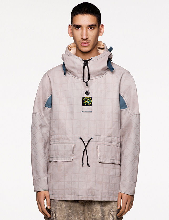 Model wearing beige check and paint splatter print pants and a same print off white anorak with light blue details, standing collar, front hand pockets with flap and central buttoned strap bearing the Stone Island badge.