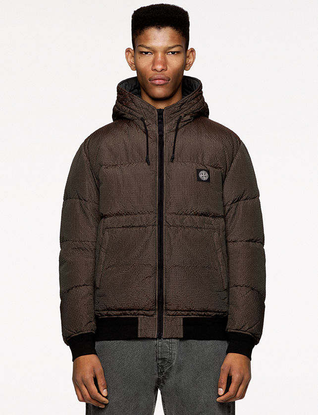 Model wearing gray denim pants and a brown down jacket with hood and drawstring, Stone Island patch at left chest and black ribbed cuffs and bottom band.