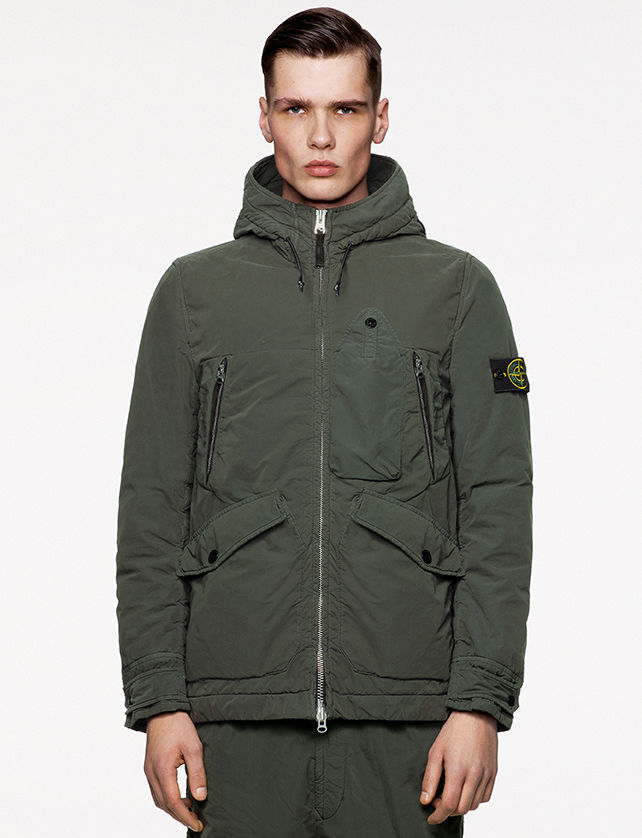 Model wearing military green pants and a matching jacket with hood and drawstring, zipper fastening, multiple pockets and the Stone Island badge on the upper left arm.