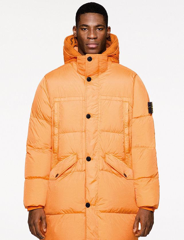 Model wearing a long orange down jacket with hood, button fastening, chest pockets and slanting pockets with flap and button fastening.