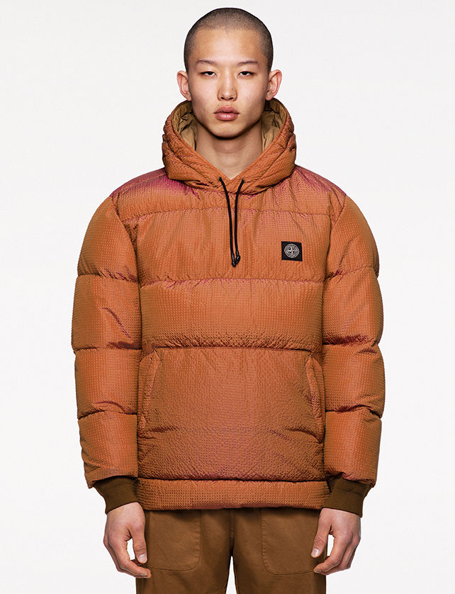 Model wearing camel pants and an orange padded anorak with hood and drawstring, brown ribbed cuffs, pouch pocket with slanting entrances and Stone Island patch at left chest.