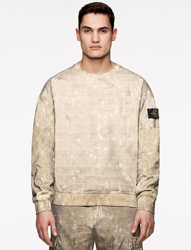 Model wearing beige check and paint splatter print pants and a matching crewneck sweatshirt with low shoulder line, ribbed neckline, cuffs and bottom band.