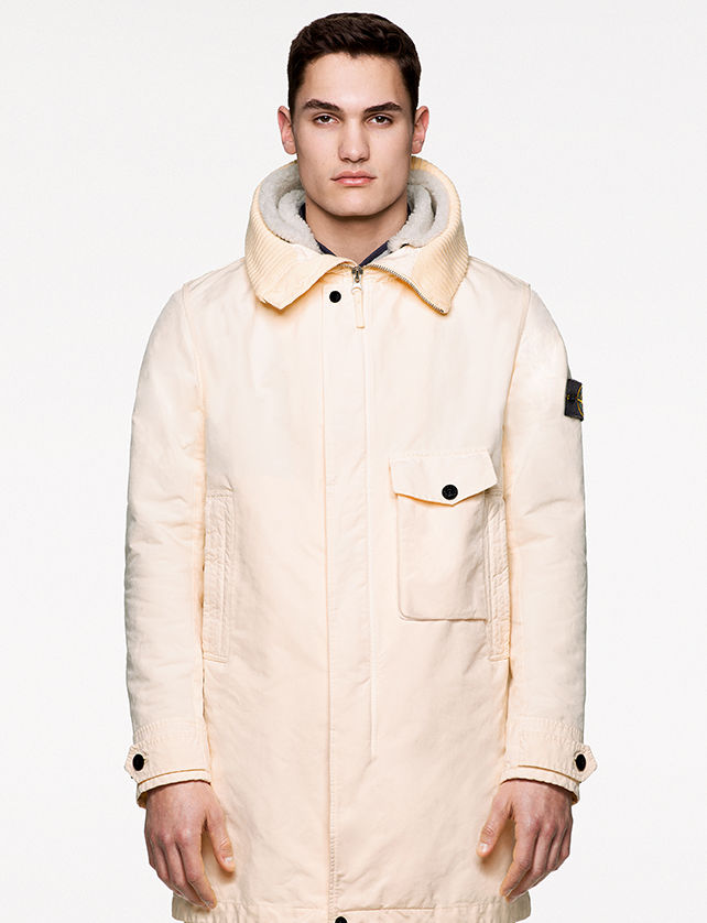 Model wearing an off white jacket with wide collar, hidden zipper closure, hand pockets and one bellows chest pocket with flap and button fastening.