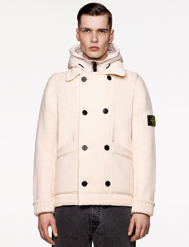 Model wearing dark gray denim pants and an off white knit jacket with collar, hood, double breasted buttons fastening, ribbed cuffs and the Stone Island badge on upper left arm.