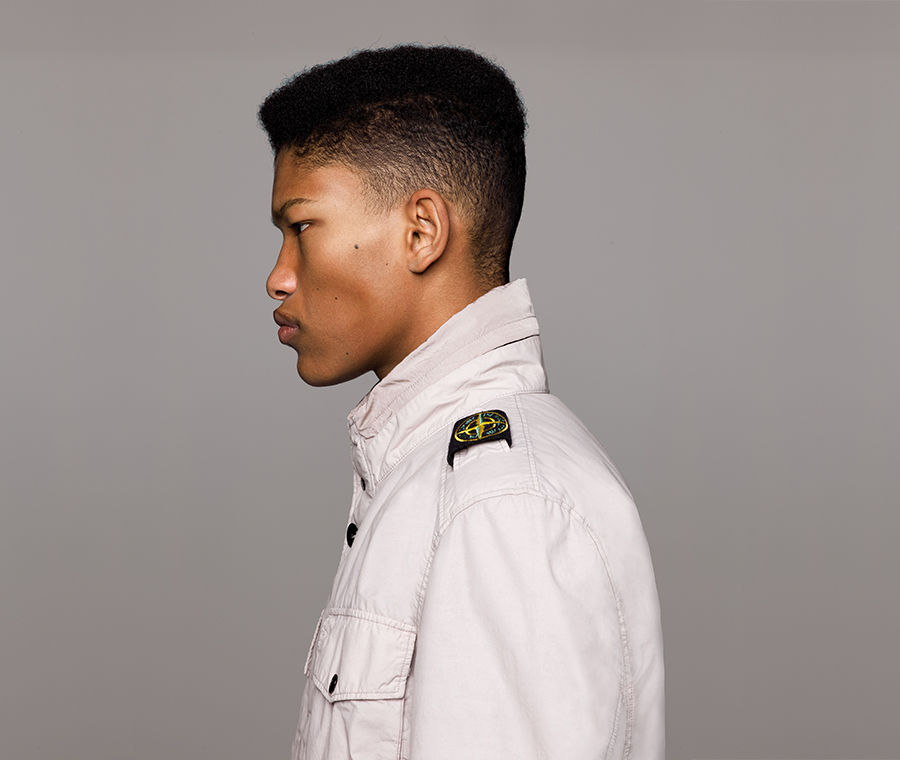 Side view of model wearing an off white jacket with standing collar, bellows chest pocket with flap and snap fastening and Stone Island badge on left shoulder.