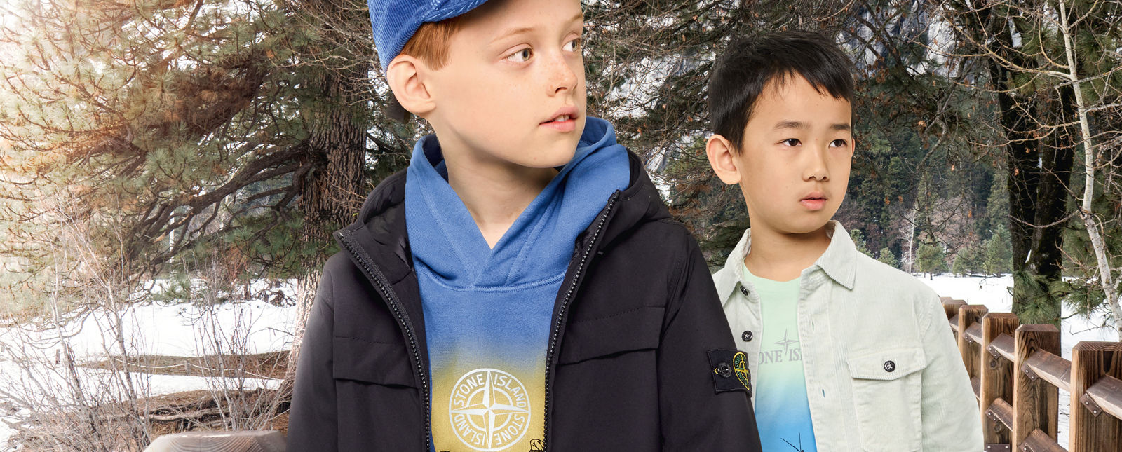 Two junior models, one wearing a hooded blue sweatshirt with a colorful print and the Stone Island compass logo, a blue cap and a dark colored jacket with zipper fastening, the other one wearing a light green t shirt with a colorful print on the front and