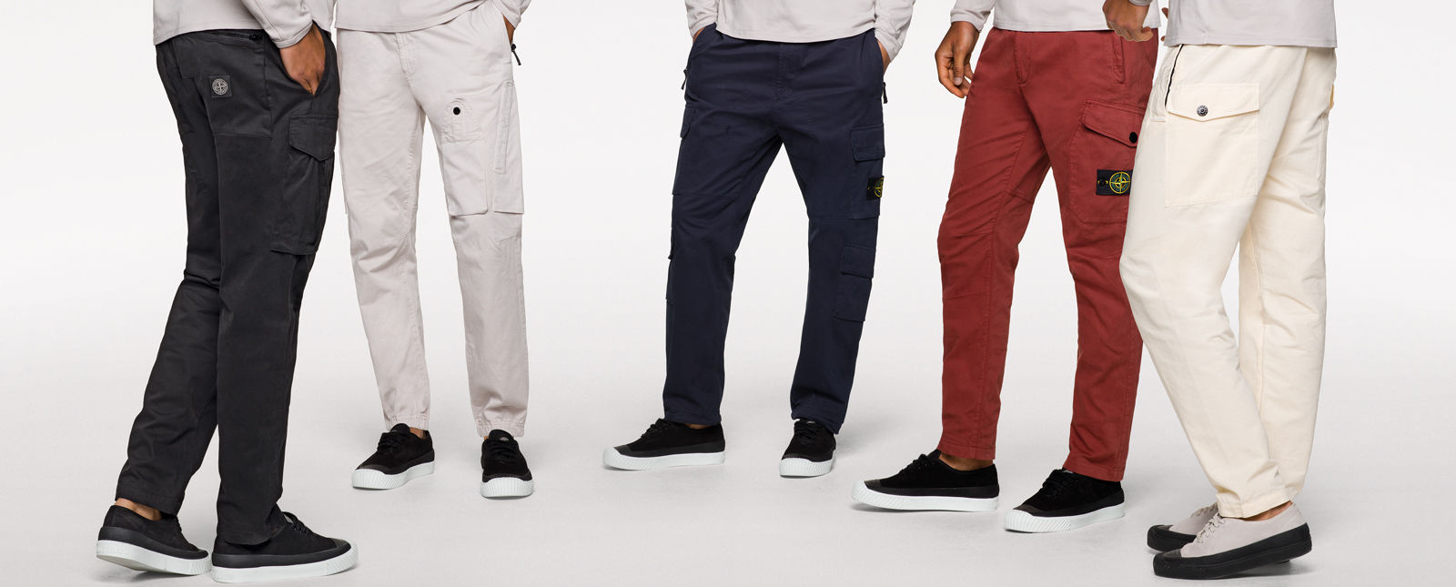 Five models standing in a semi circle and wearing off white tops, sneakers and different styles of cargo pants in black, white, dark blue, brick red and cream.