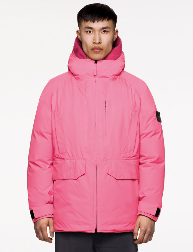 Model wearing dark colored pants and a pink hooded jacket with standing collar, zipper fastening, welt chest pockets, hand pockets with flap and strap at cuffs.