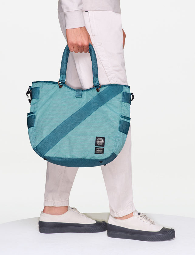 Side view of model wearing white pants with elasticized cuffs, black and white sneakers and a light blue tote bag with handles, side pockets and the Stone Island patch.