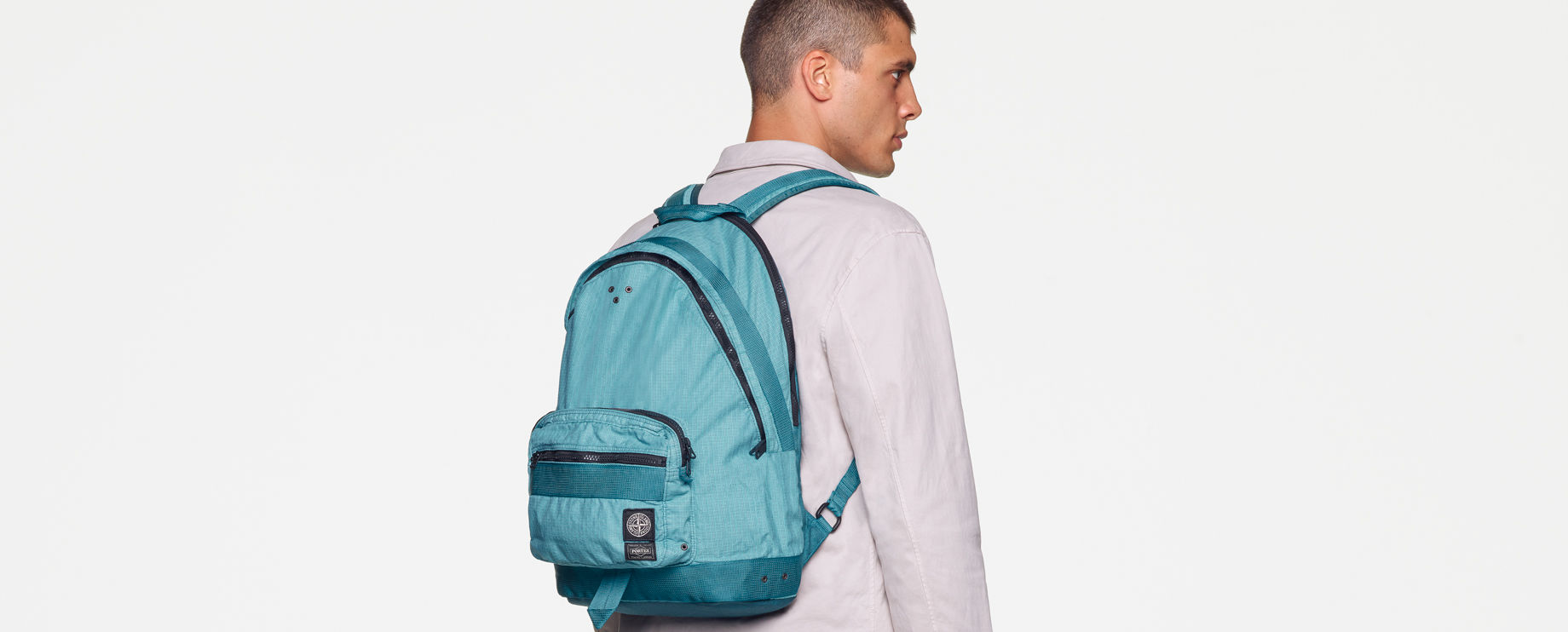 Back view of model wearing a white sweatshirt, white pants with the Stone Island patch on the back pocket and a light blue waist bag with black zippers and multiple pockets, worn over the shoulder.