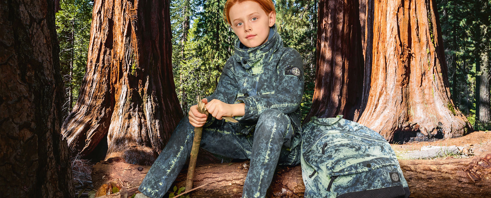 Junior model wearing blue and cream camouflage pants, a matching parka with hood, button fastening and a matching camouflage backpack with zipper fastening and patch pocket on front.