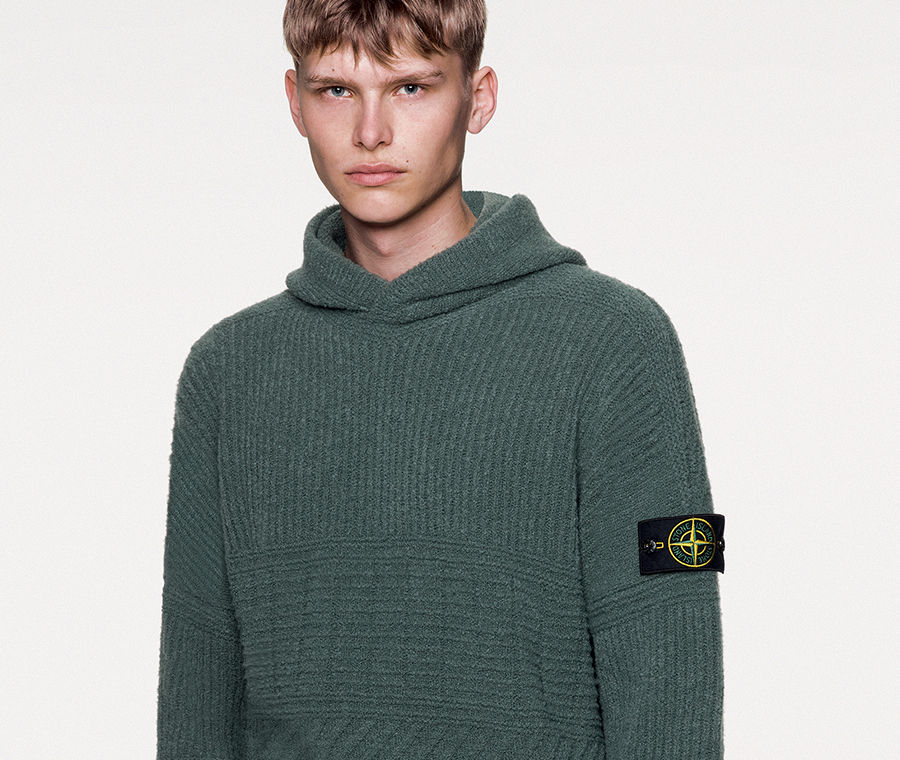Model wearing dark colored knit trousers with slanting hand pocket and a dark green hooded sweater with dropped shoulders, stitching motifs on the bust and sleeves and ribbed cuffs and bottom band.