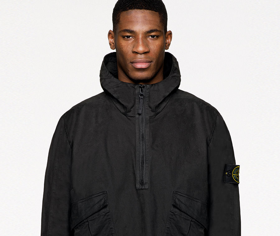 Model wearing black cargo pants and a matching anorak with standing collar, half zipper, two slanting patch pockets with flap and the Stone Island badge on upper left arm.
