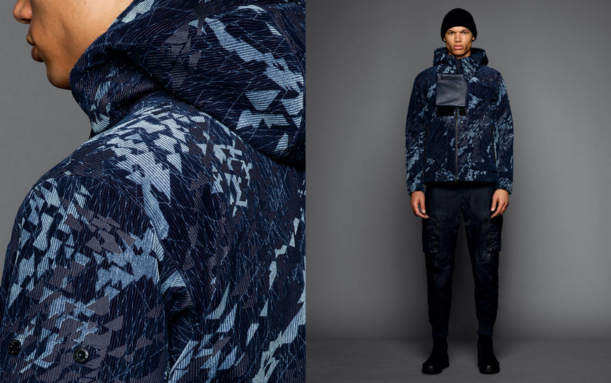 Two shots of the same model, one showing the detail of a blue geometric print jacket, the other one with the model wearing black boots, dark colored cargo pants, a blue geometric print hooded jacket with chest detail and a black beanie.