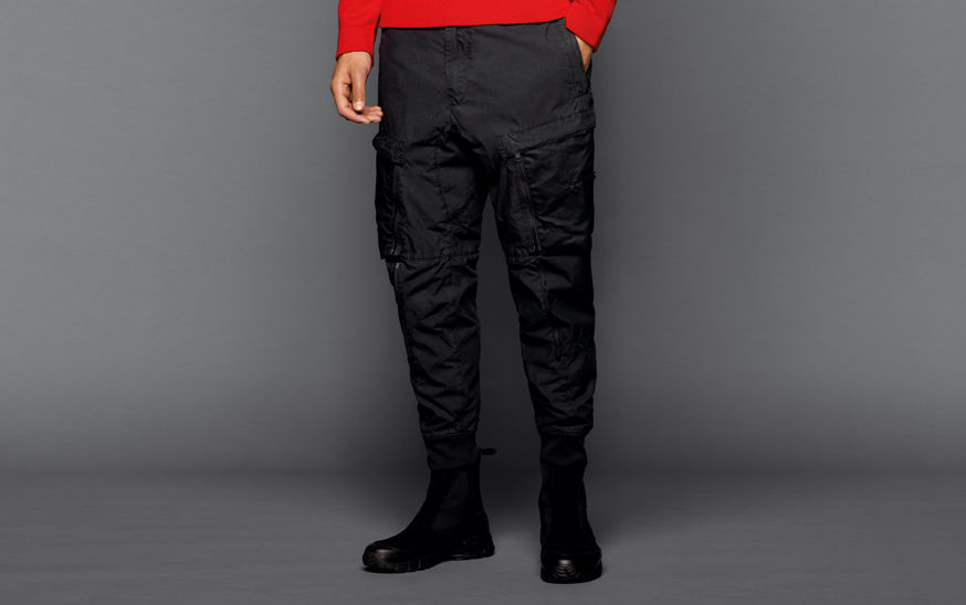 Close up of a model wearing black boots, black cargo pants with multiple pockets and a red top with long sleeves.