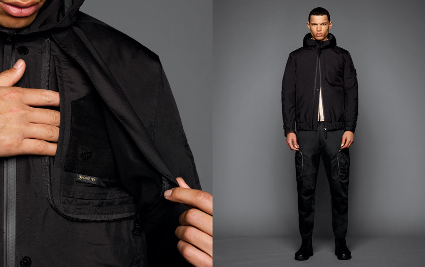 Two shots of the same model, one showing the details of a chest pocket, the other one with the model wearing black boots, black cargo pants, an off white top and a black jacket with hood, zipper fastening and straps at cuff.
