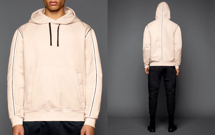 Two shots of the same model, one showing the front of a cream sweatshirt with hood and dark piping on the shoulders and sleeves, the other one showing the back of  black cargo pants and an off white sweatshirt with dark piping on the shoulders and down th